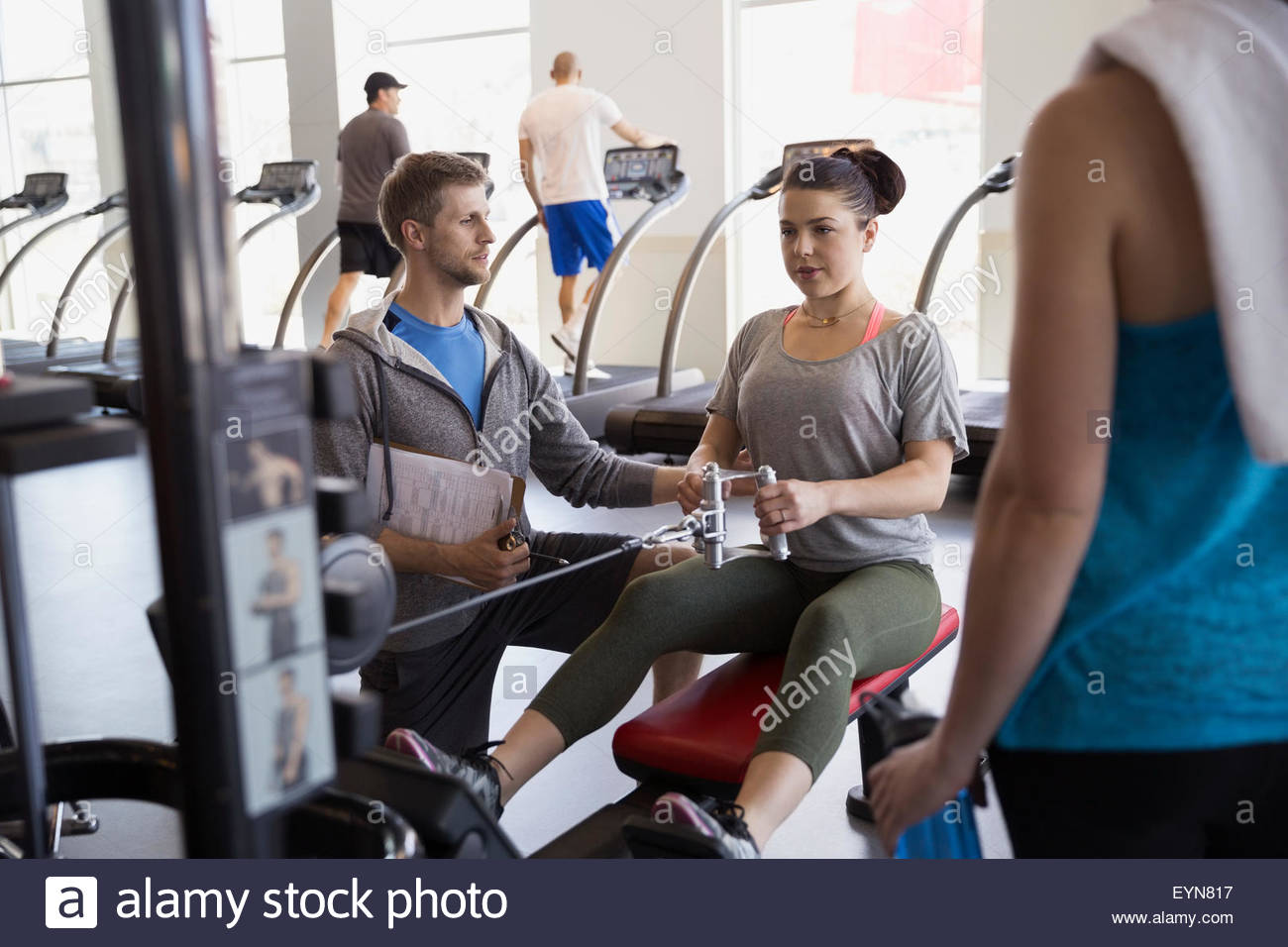 Personal trainer guiding woman seated cable row gym - Stock Image