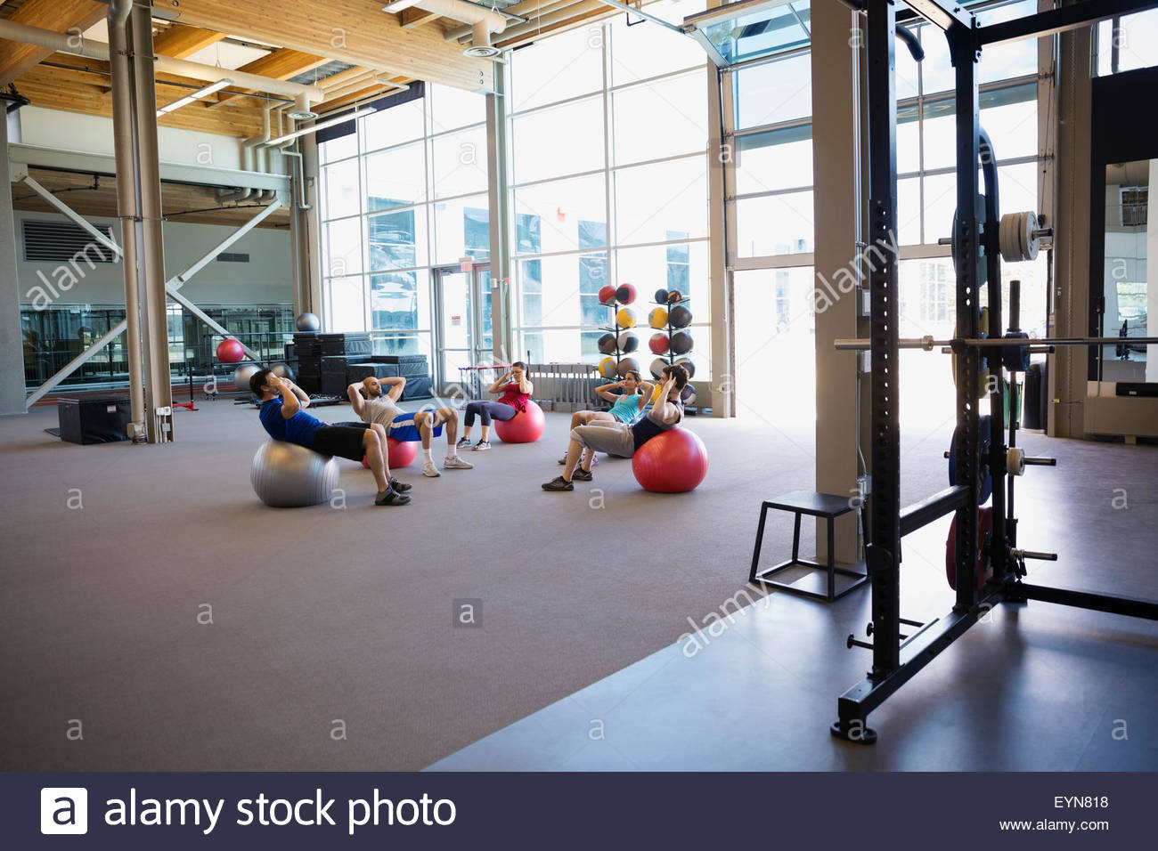 Exercise class doing fitness ball sit-ups gym - Stock Image