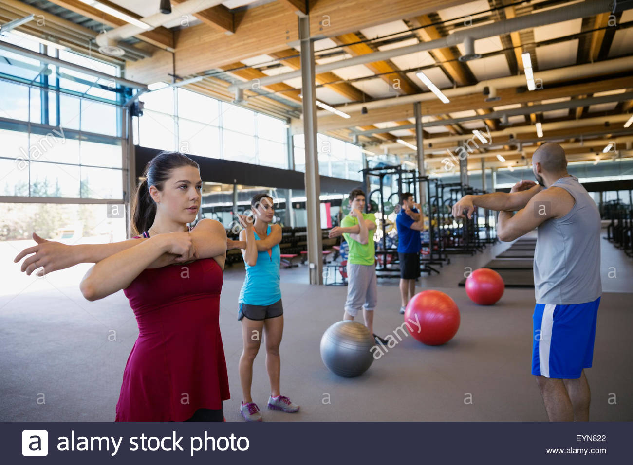Exercise class stretching arms in gym - Stock Image