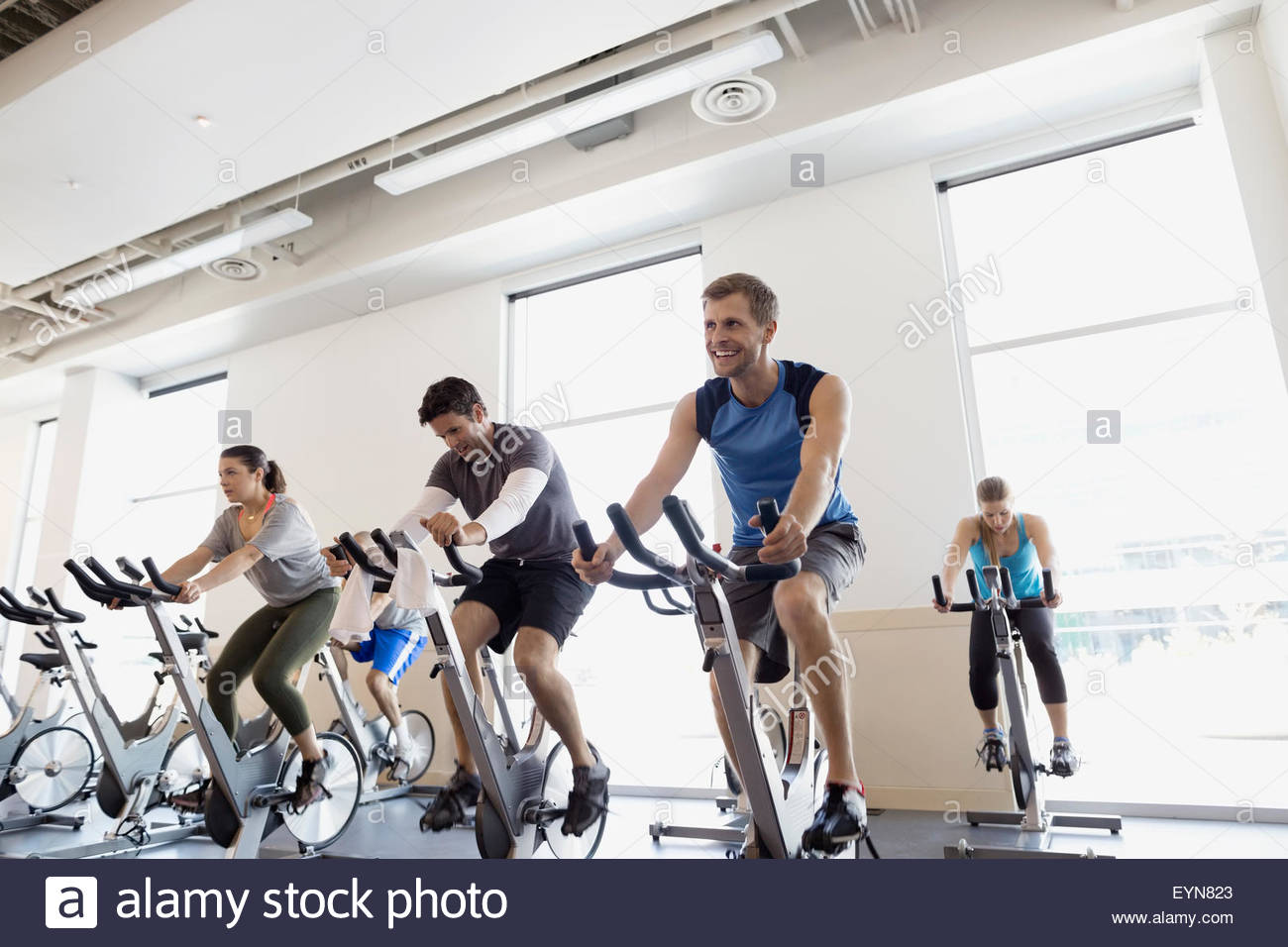 Spin class on stationary bikes at gym Stock Photo