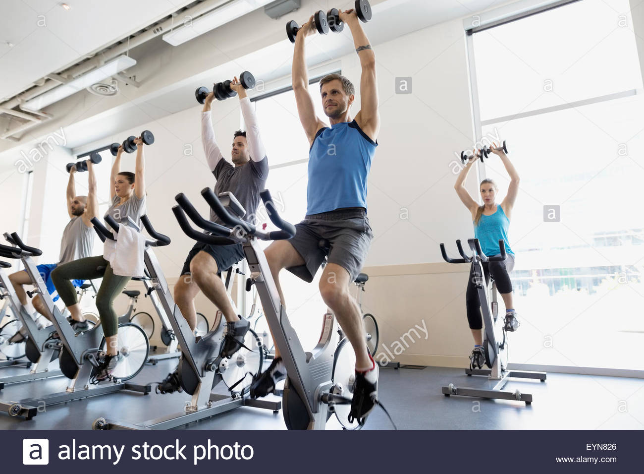 Spin class holding barbells overhead stationary bikes gym - Stock Image