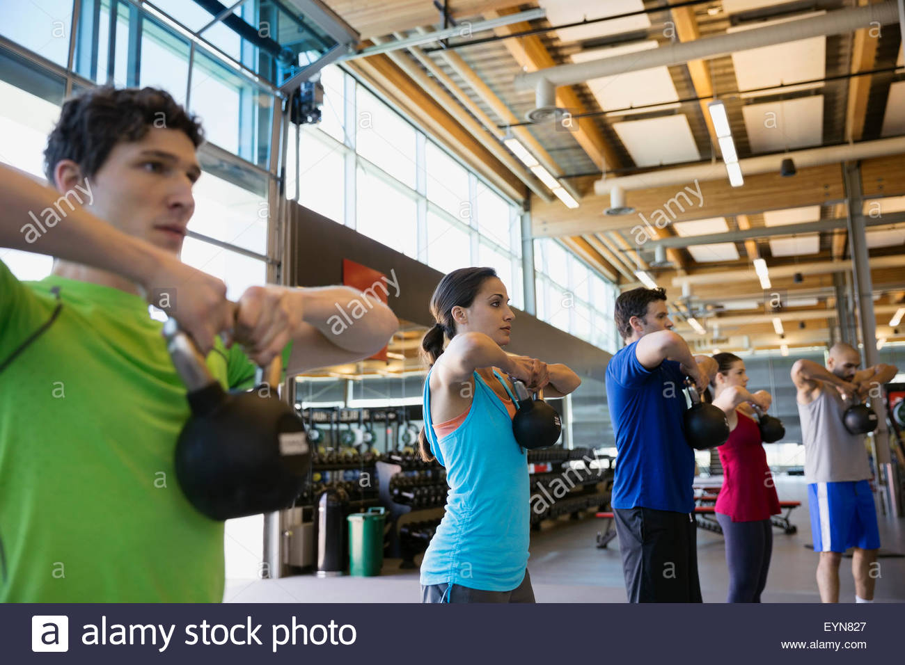 Exercise class doing kettlebell pulls in a row - Stock Image