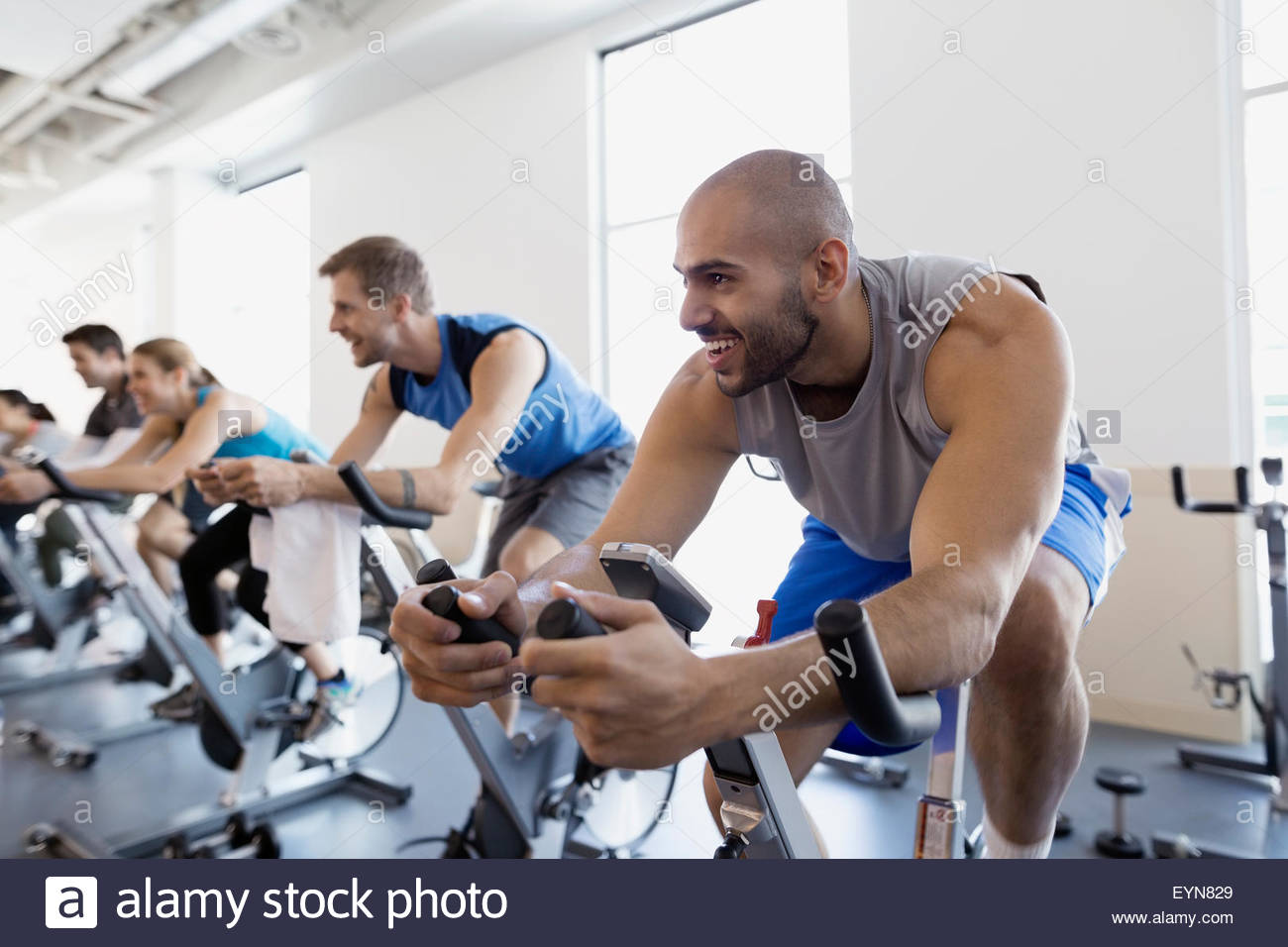 Smiling man enjoying spin class stationary bike gym - Stock Image