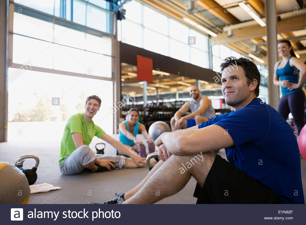 Exercise class stretching in gym - Stock Image