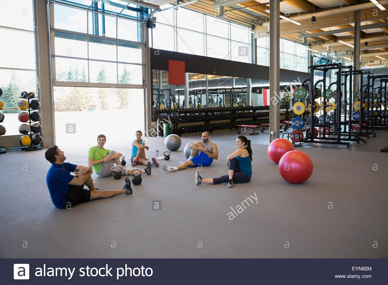 Exercise class stretching in seated twist at gym - Stock Image