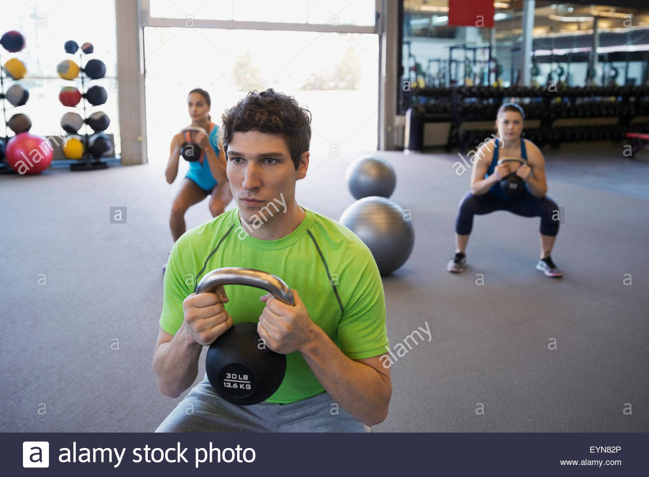 Serious exercise class doing kettlebell squats at gym - Stock Image