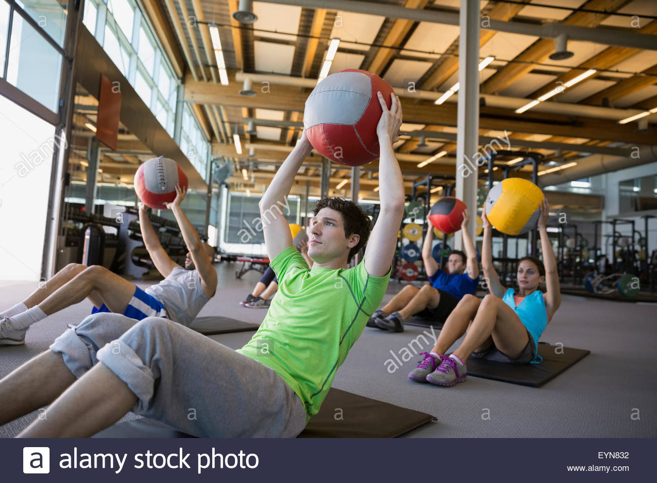 Exercise class holding medicine balls overhead in gym - Stock Image