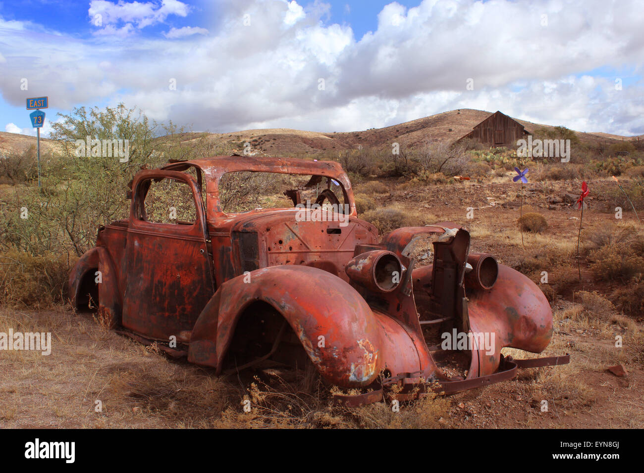 Old car rusting in Desert Landscape with Barn in Background - Stock Image