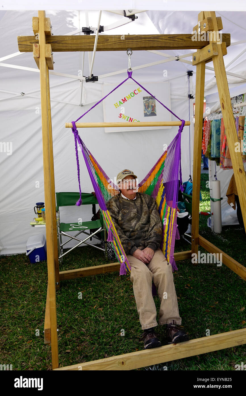 Orville Strang relaxes in one of the hammock swings he is selling at the Art Fiesta, New Smyrna Beach, Florida - Stock Image