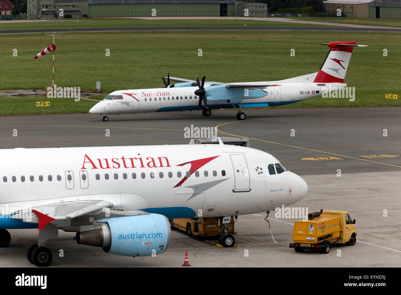 Bombardier Dash 8-Q402 and Airbus A320 Austrian on runway , Blue Danube Airport Linz - Stock Image
