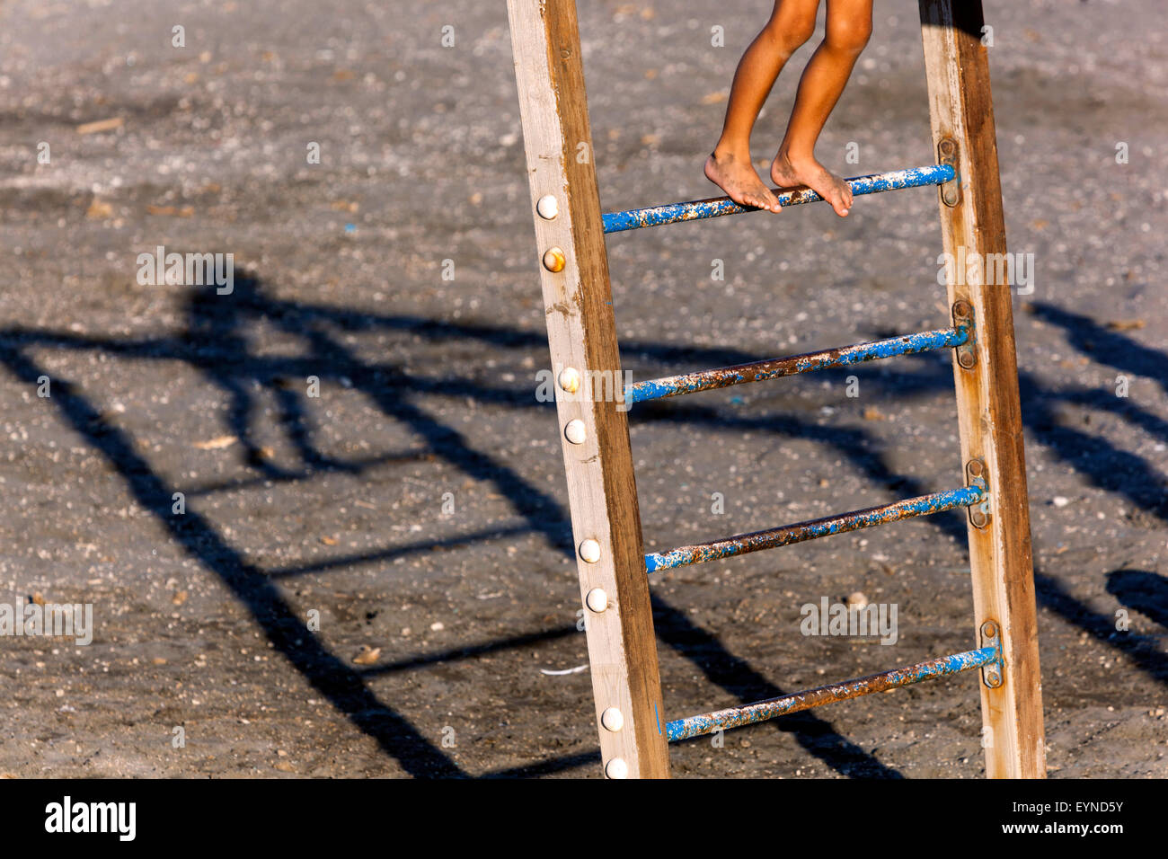 Boy feet on children's climbing frame and projecting a shadow, Santorini beach, Greece - Stock Image