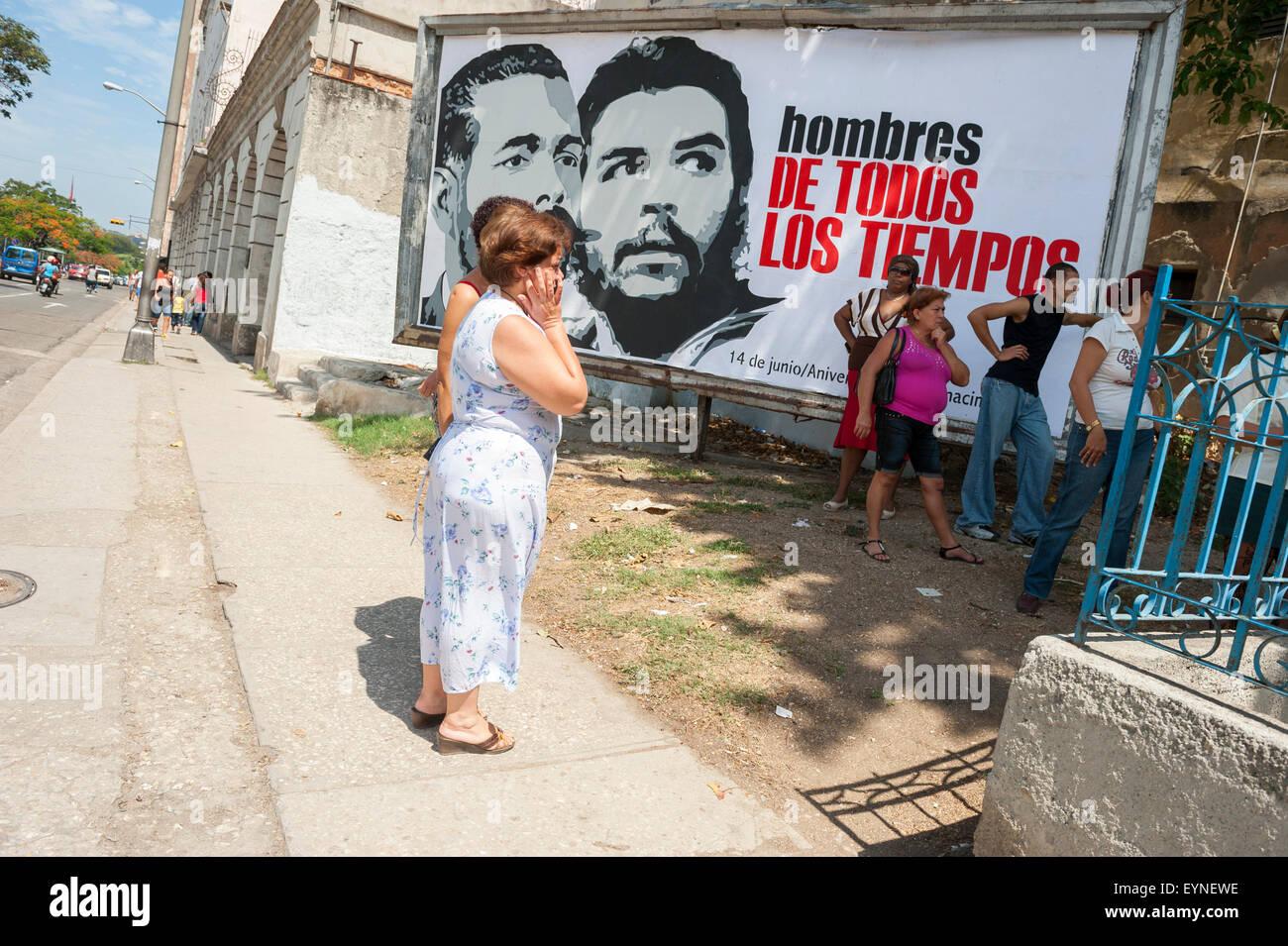 HAVANA, CUBA - JUNE, 2011: Cubans line up in front of a billboard of propaganda featuring revolutionary leaders. - Stock Image