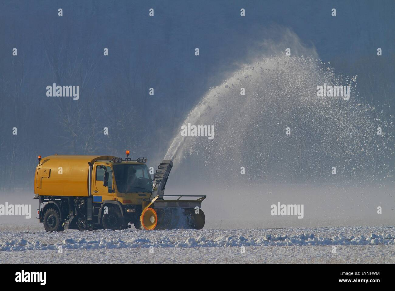Snowplow removing snow at an airfield in the winter - Stock Image