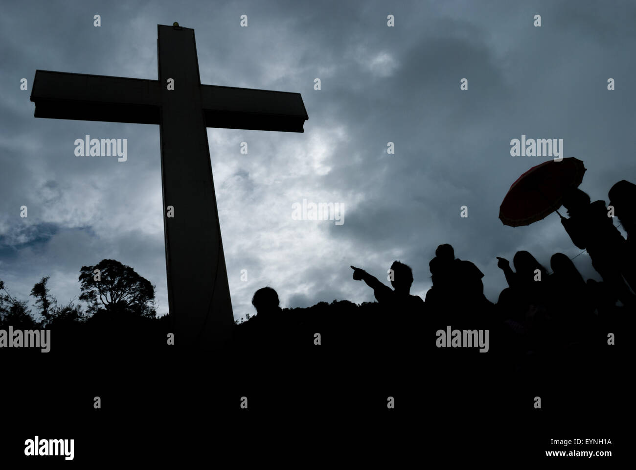 Giant Christian Cross and people silhouetted against the sky on a rainy day. - Stock Image