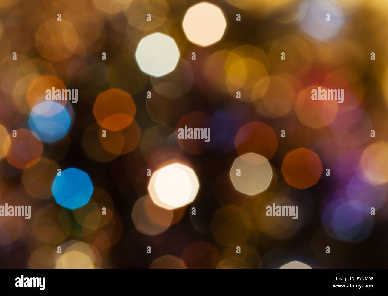 abstract blurred background - dark brown shimmering Christmas lights of electric garlands on Xmas tree Stock Photo