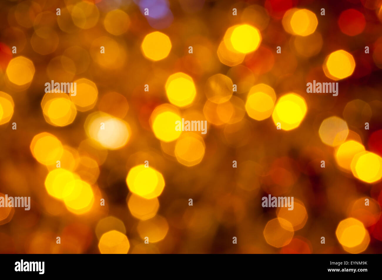 abstract blurred background - dark brown, yellow and red flickering Christmas lights of electric garlands on Xmas - Stock Image