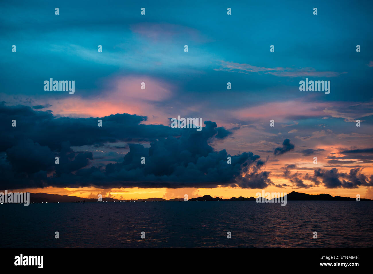A dramatic sunset with mountains and clouds in Alor island nearby Flores, reach of colors and contrast photographed - Stock Image