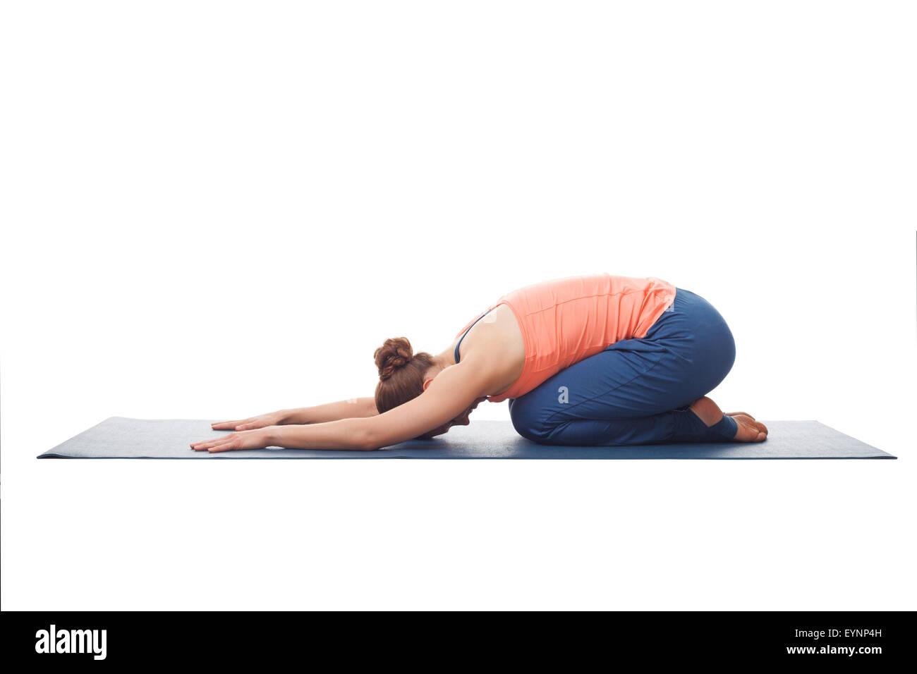 Beautiful sporty fit yogi girl practices yoga asana balasana - Stock Image