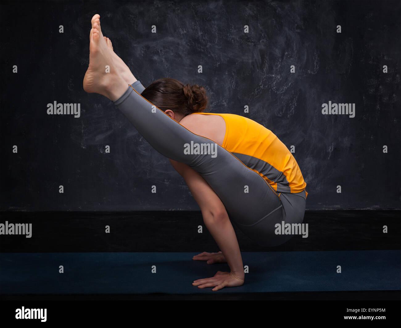 Beautiful sporty fit yogi girl practices yoga asana titibhasana - Stock Image
