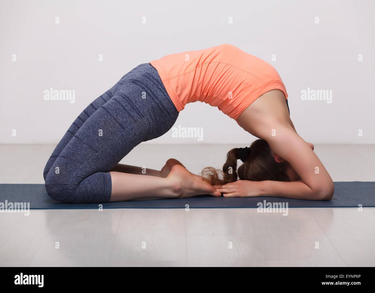 Beautiful sporty fit yogi girl practices yoga asana Kapotasana - Stock Image