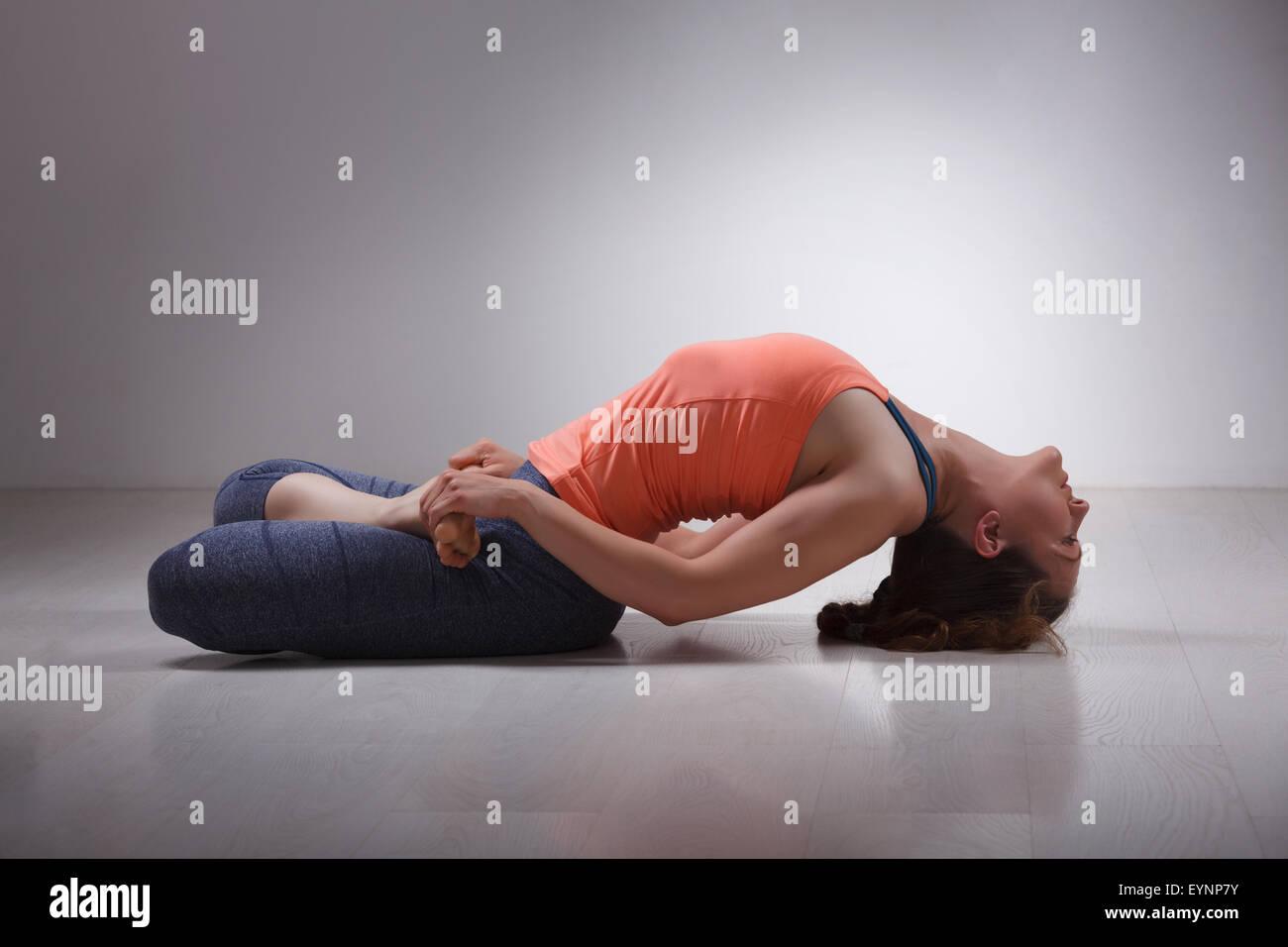 Beautiful sporty fit yogi girl practices yoga asana Matsyasana - Stock Image