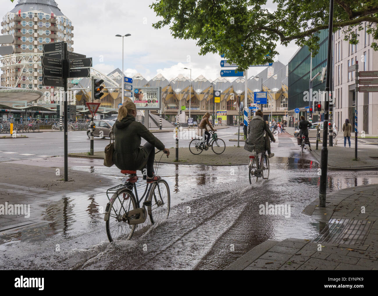 Rotterdam, Netherlands - young women try to avoid getting wet as they ride through flooded cycle lanes in front - Stock Image