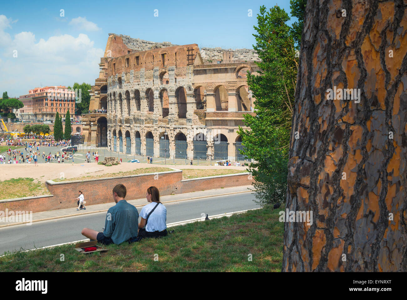 Colosseum Rome, view of tourists sitting in the Parco del Celio facing the Colosseum in the centre of Rome, Italy. - Stock Image