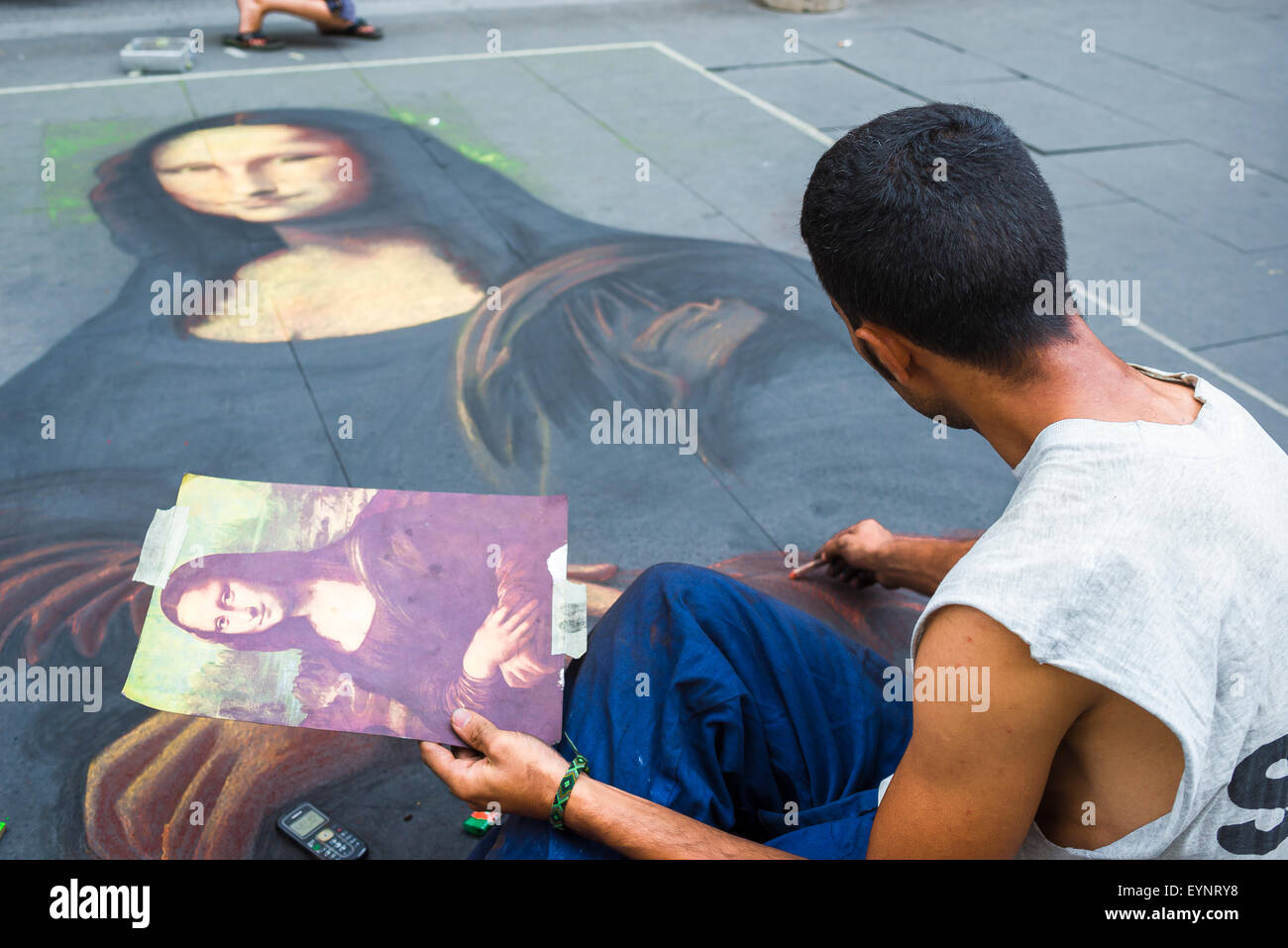 Mona Lisa, a pavement artist puts the finishing touches to a drawing of the Mona Lisa in Rome's Via Del Corso, - Stock Image
