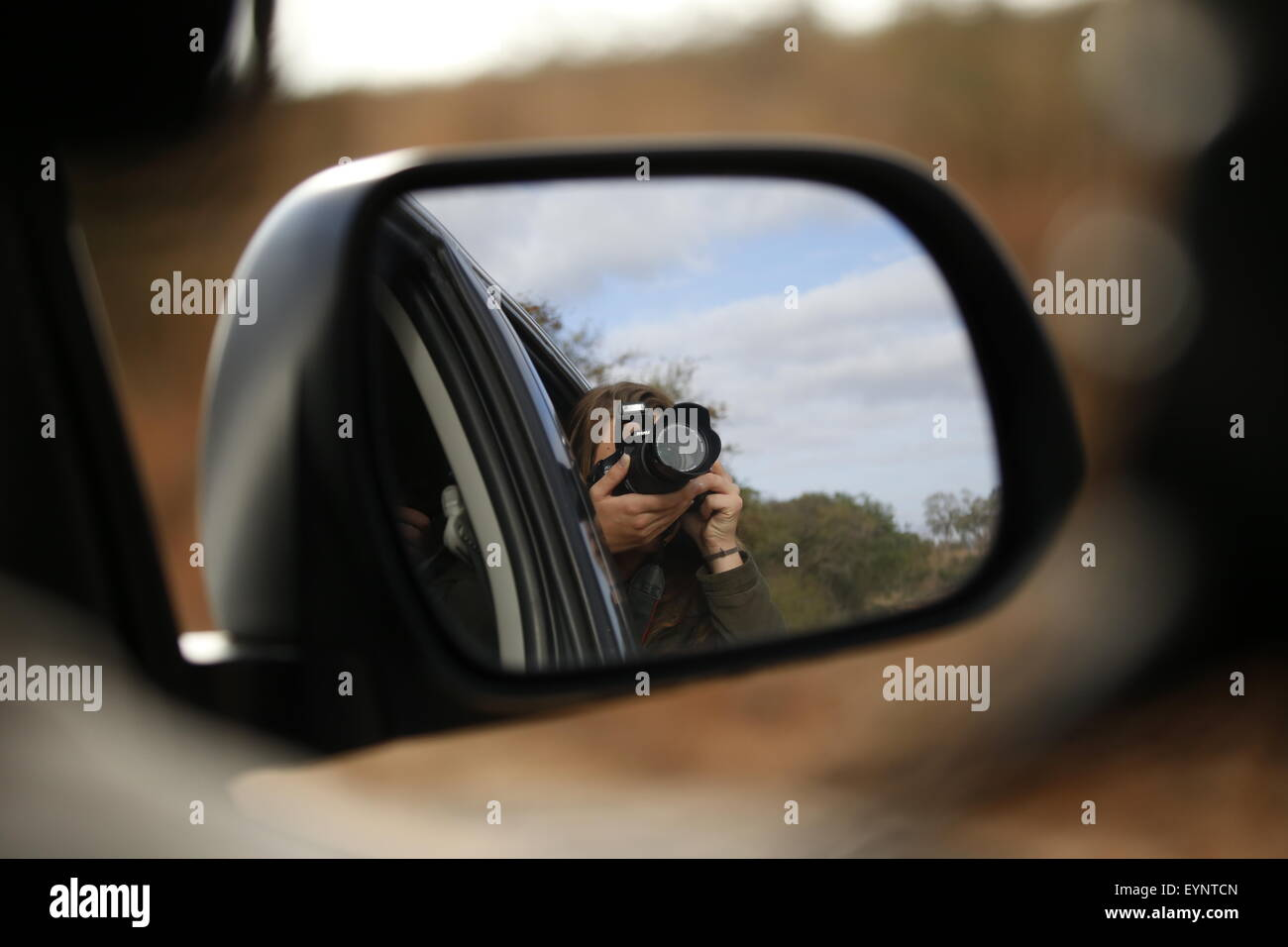 A reflection in a car wing mirror of a pretty lady taking