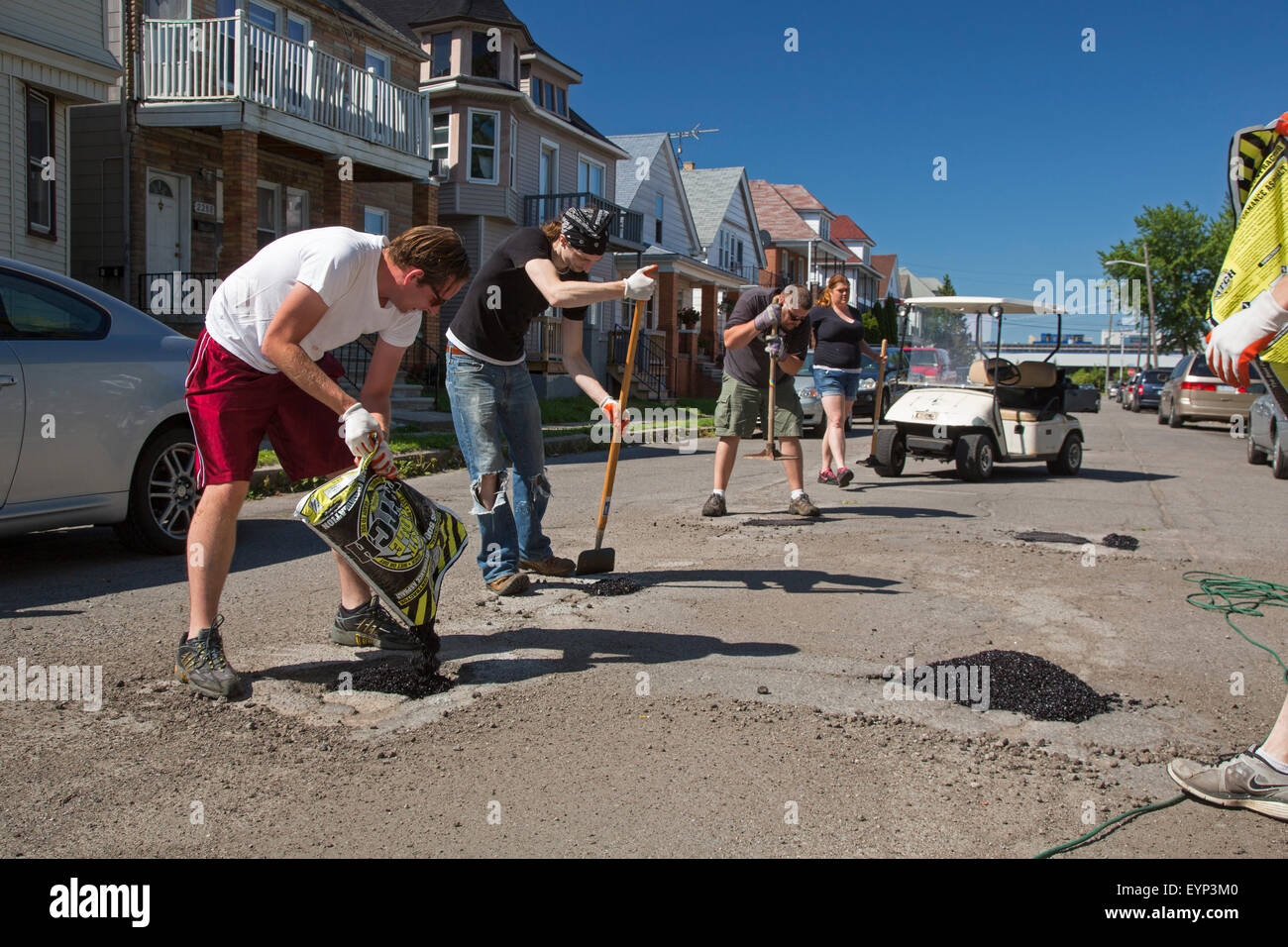 Hamtramck, Michigan - Members of the Hamtramck Guerrilla Road Repair crew fill potholes on the city's streets. - Stock Image