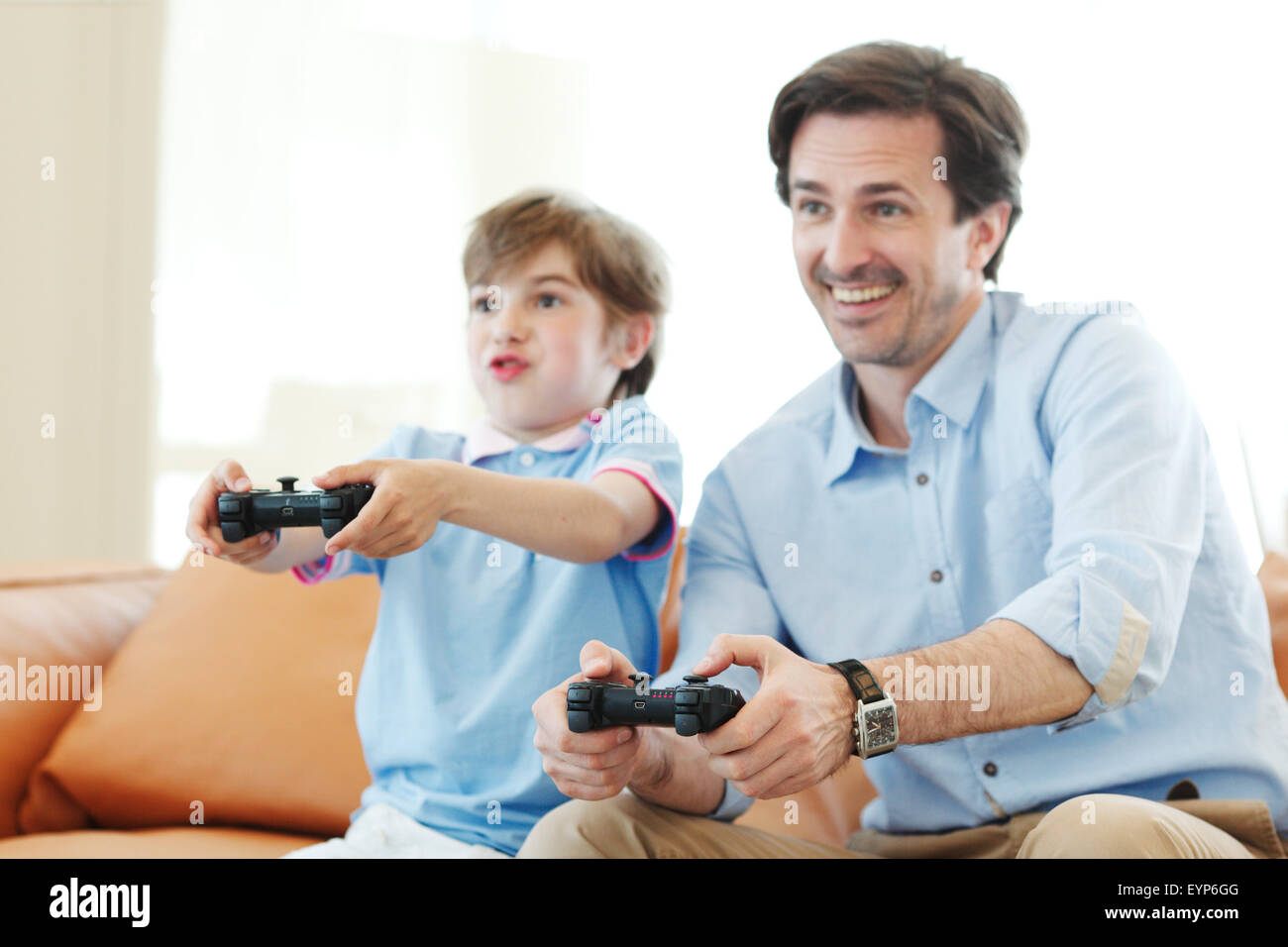 father and son play video game - Stock Image