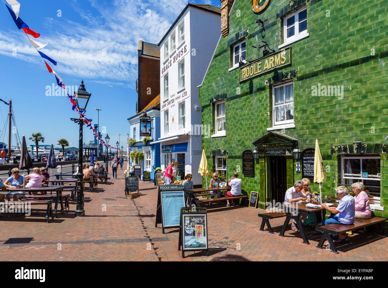People sitting outside the Poole Arms pub on The Quay in Poole, Dorset, England, UK - Stock Image