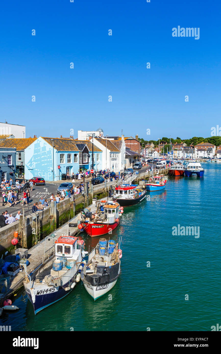 People sitting outside pubs and bars on Custom House Quay in Weymouth, Jurassic Coast, Dorset, England, UK - Stock Image