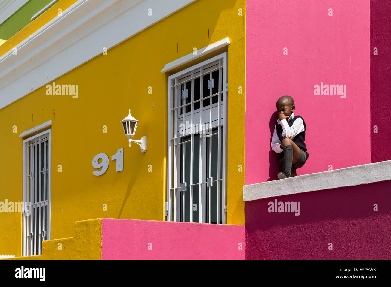 Young boy on stoop of a typical brightly-colored house on Wale St in the Bo-Kaap neighborhood of Cape Town - Stock Image