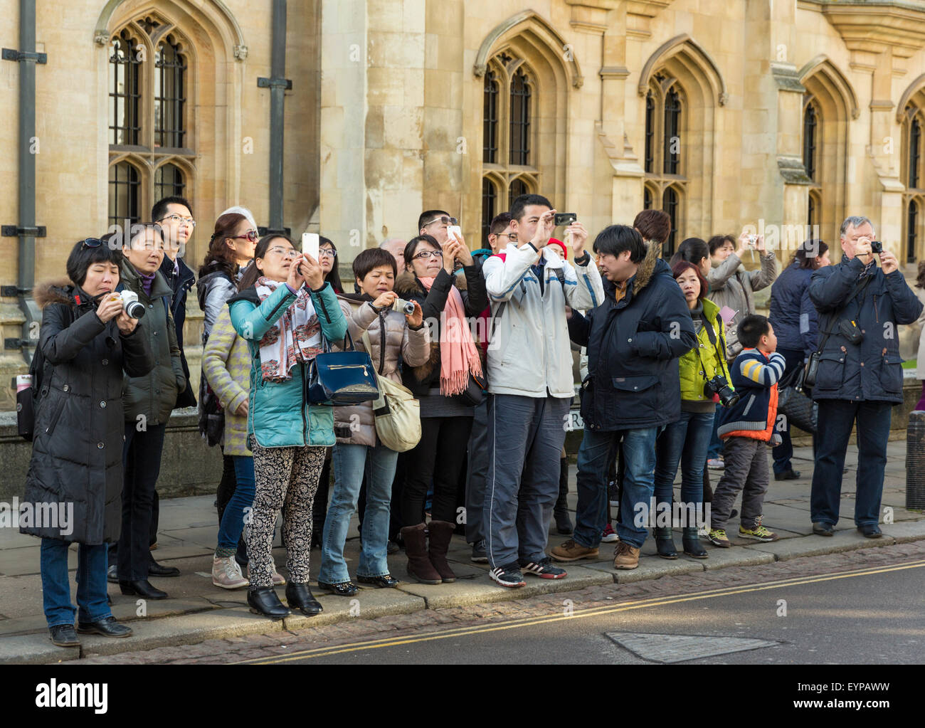 Group of Chinese tourists on Cambridge St in Cambridge England pause together to take photographs - Stock Image