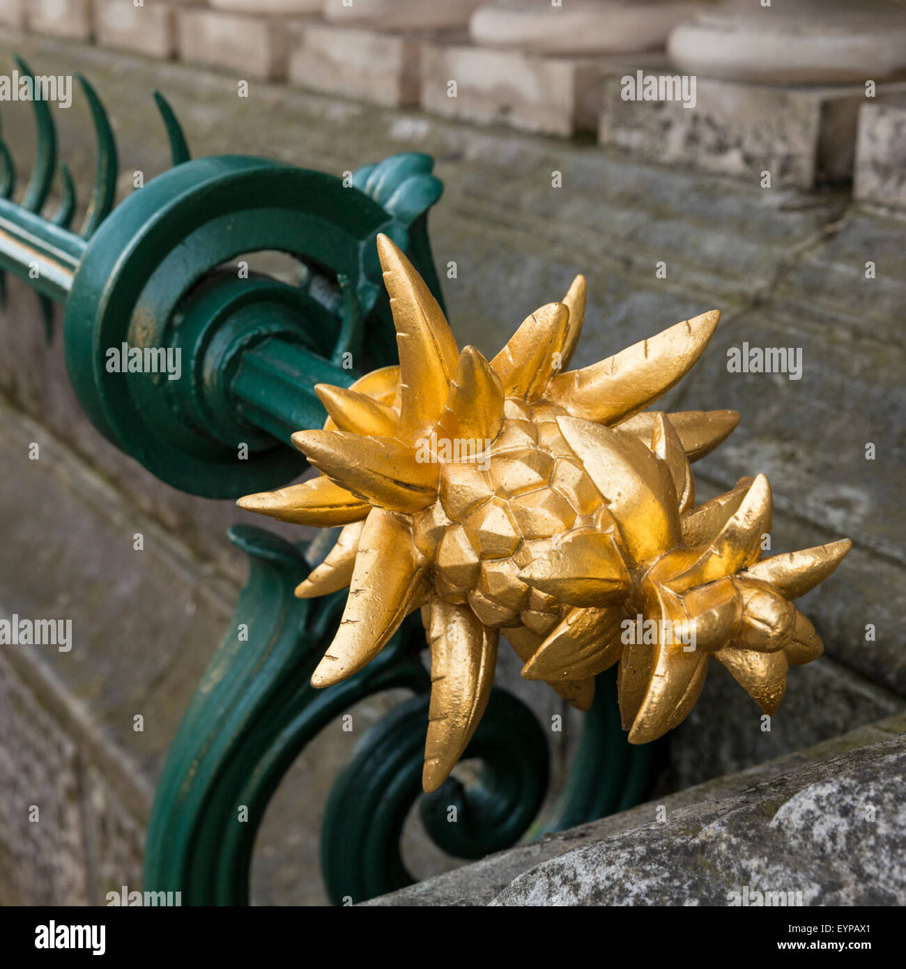 Spiked gilt pineapple at end of spiked fence limiting entry to the Fitzwilliam Museum in Cambridge, England, UK - Stock Image