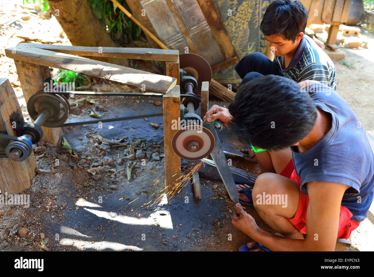 Two young Burmese  male villager 's using primitive machinery to a grindstone to put  the cutting edge for farm - Stock Image