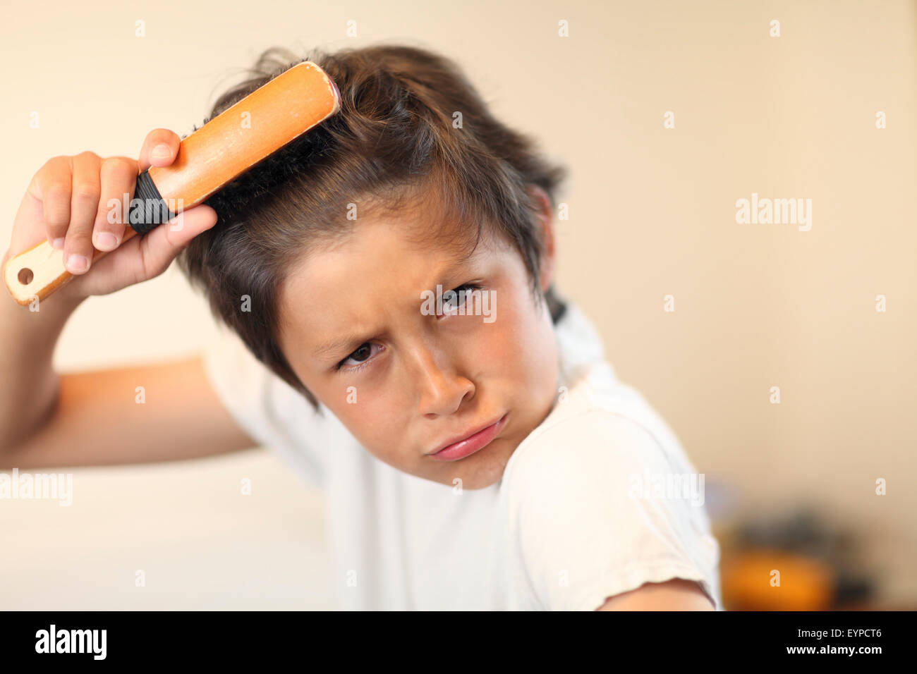 Bed time - boy brushes his hair - very shallow depth of field - Stock Image