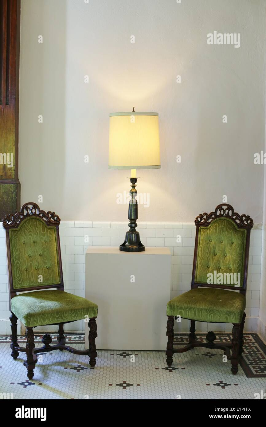 Two green antique chairs with a lamp between them. - Stock Image