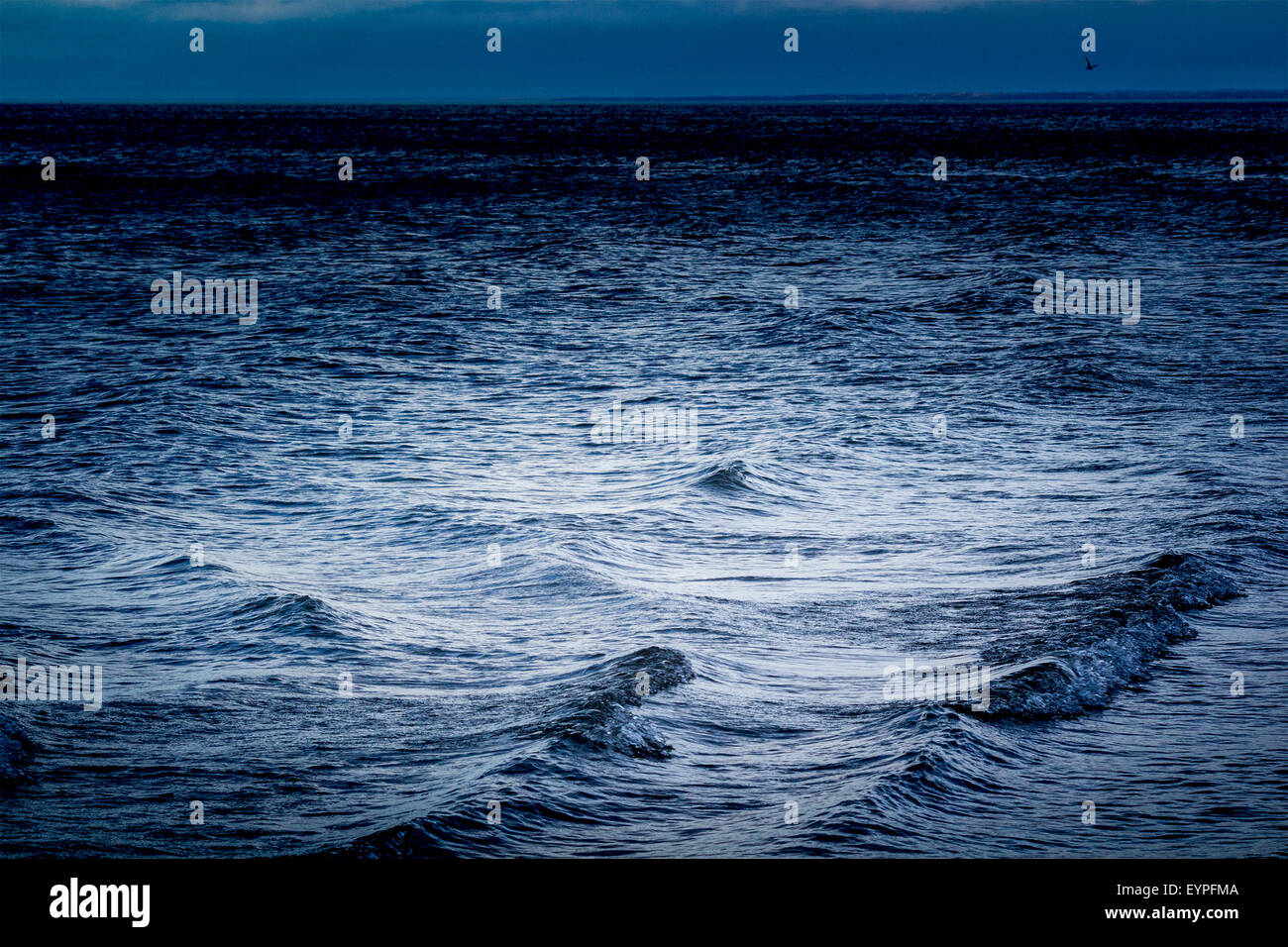 Waves coming into shore on Lake Huron with moonlight bouncing off of the water - Stock Image