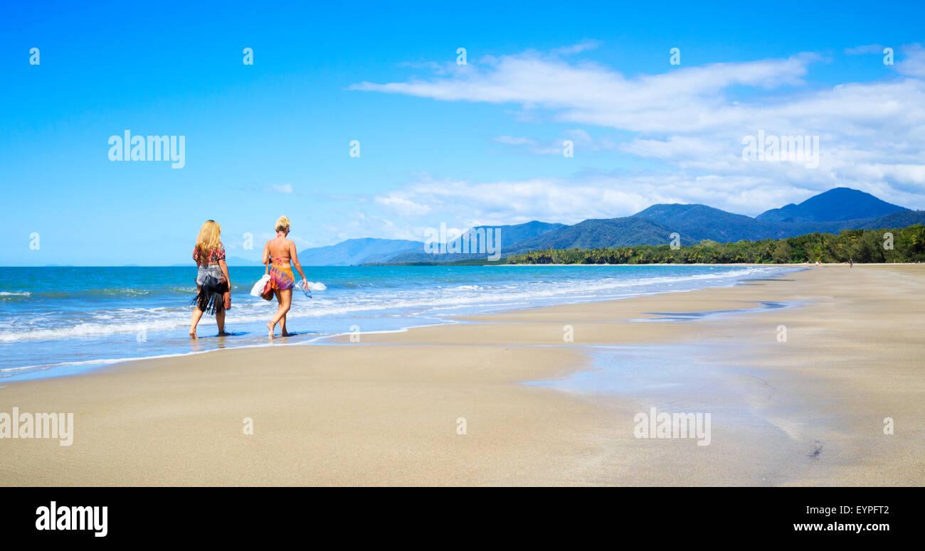 Two young women walking along Four Mile Beach in Port Douglas, Queensland, Australia - Stock Image