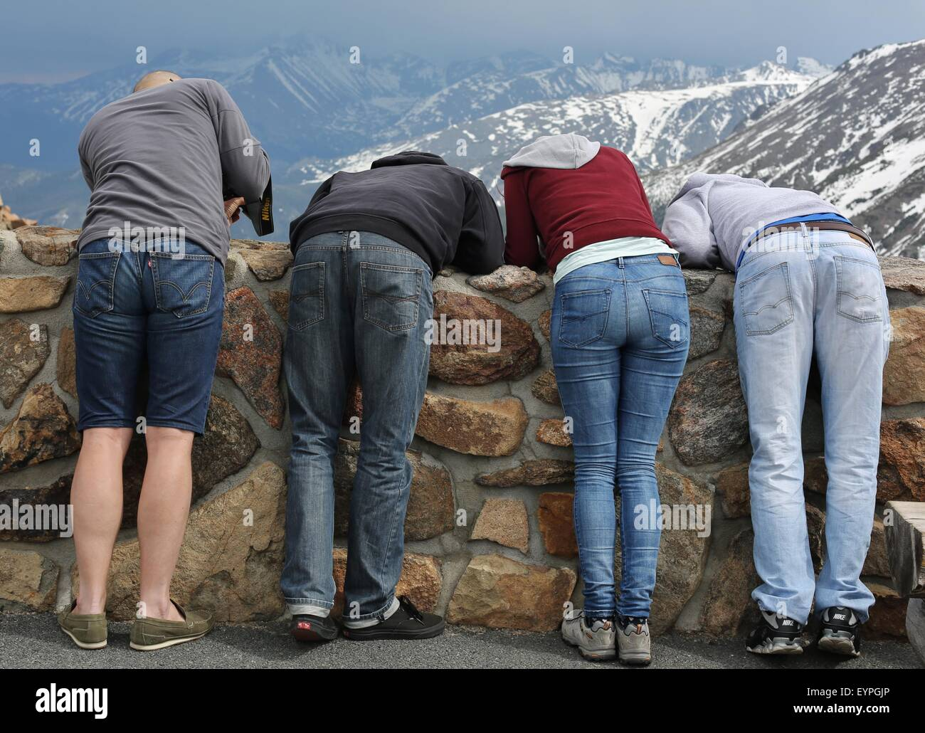 Tourists at Rocky Mountain National Park in Colorado leaning over a wall to look at something. Stock Photo