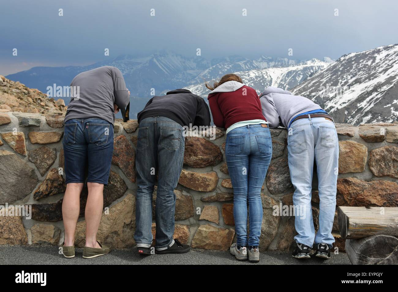 Tourists at Rocky Mountain National Park in Colorado leaning over a wall to look at something. - Stock Image