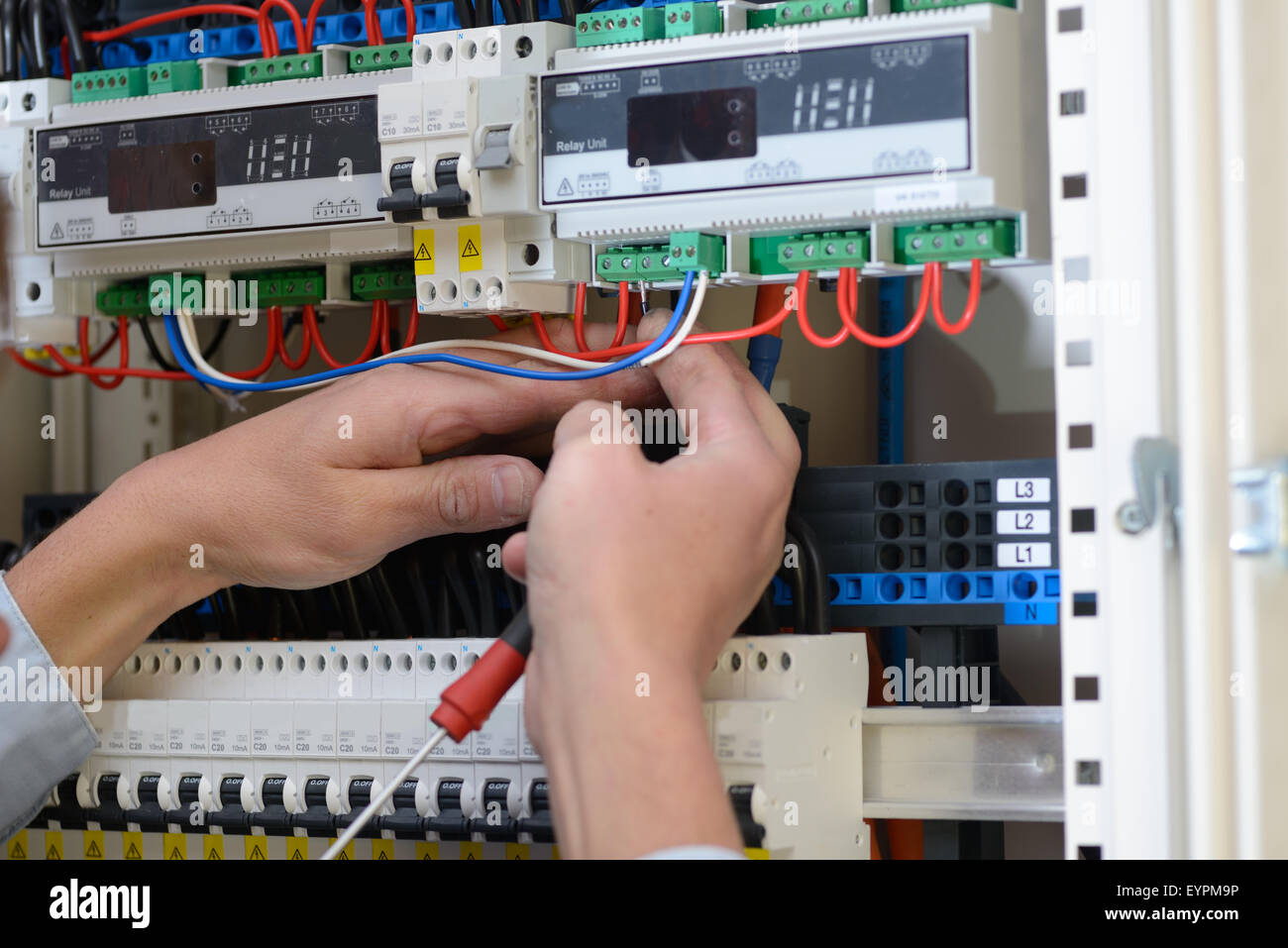 Electrician wiring up a switchboard in a new building Stock ... on
