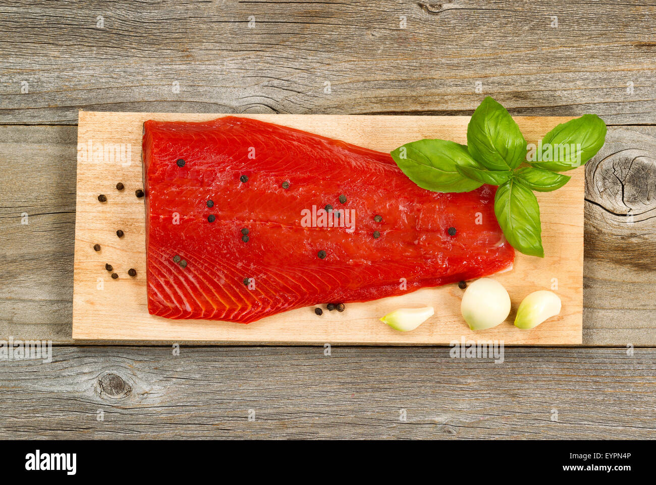 Top view shot of fresh red salmon fillet on cedar cooking board with peppercorn, garlic and basil. Aged wood underneath. - Stock Image