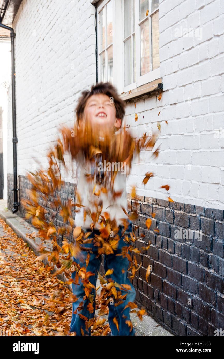 Caucasian child, boy enjoying himself in a road by wall, by taking handfuls of autumn fallen leaves and throwing Stock Photo
