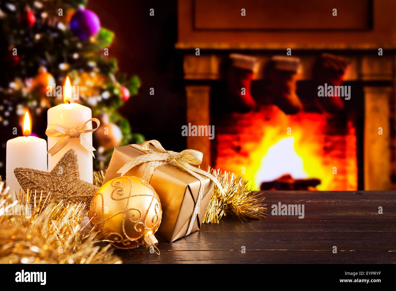 Christmas decorations, a gift and candles in front of a fireplace. A fire is burning in the fireplace. - Stock Image