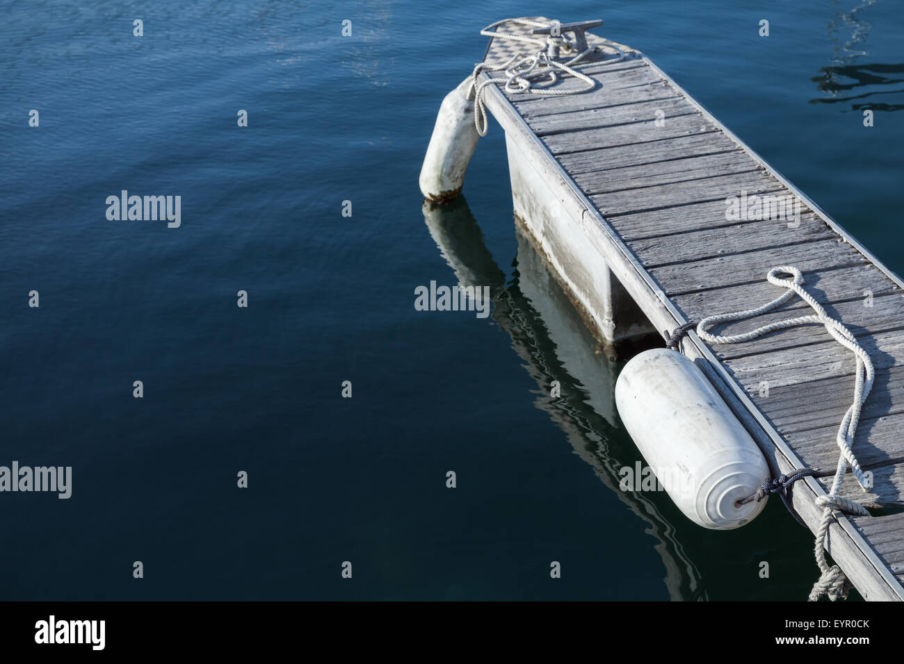Small floating pier for yachts mooring with white fenders - Stock Image