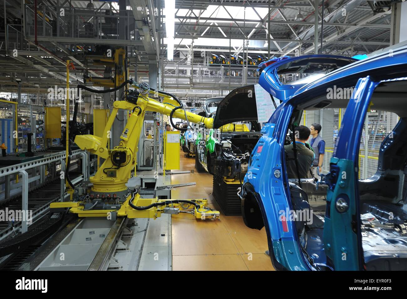 Inside a modern car factory, vehicles and parts move through the production process, robots help assemble cars - Stock Image