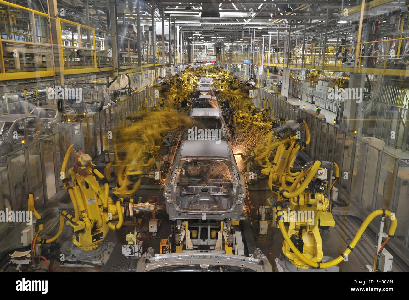 Inside a modern car factory, vehicles and parts move through the production process robots weld bare metal car bodies - Stock Image